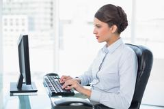 Concentrated classy brown haired businesswoman typing on a computer - stock photo