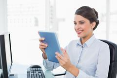 Amused classy brown haired businesswoman using a tablet pc - stock photo