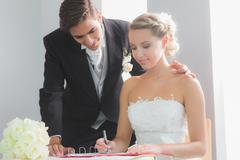 Young blonde bride sitting at table signing wedding register - stock photo