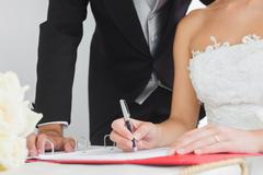 Close up of young bride signing wedding contract - stock photo