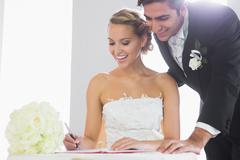 Happy young couple signing wedding register - stock photo