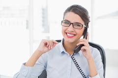 Delighted classy brown haired businesswoman answering the telephone - stock photo