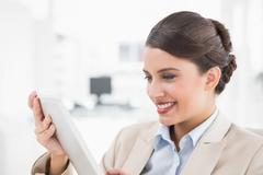 Amused smart brown haired businesswoman looking at a tablet pc - stock photo