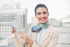 Cute smart brown haired businesswoman holding a newspaper Stock Photos