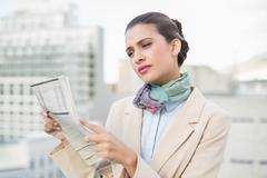 Concentrated smart brown haired businesswoman reading a newspaper - stock photo