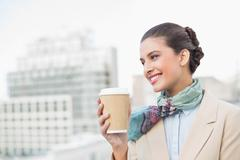 Happy smart brown haired businesswoman holding a cup of coffee Stock Photos