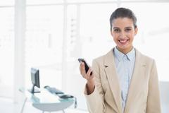 Content smart brown haired businesswoman holding a mobile phone - stock photo