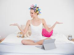 Calm natural brown haired woman in hair curlers moving her arms - stock photo