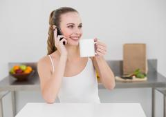 Happy young woman making a phone call and holding a mug Stock Photos