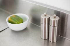 Salt and pepper on a chrome counter - stock photo