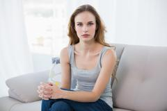 Stern young woman sitting on couch - stock photo