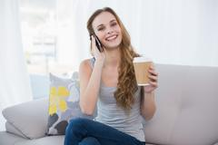 Young woman sitting on couch holding disposable cup on the phone - stock photo