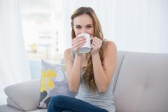 Happy young woman sitting on sofa drinking from a mug - stock photo