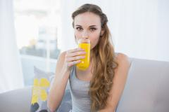 Content young woman sitting on sofa drinking glass of orange juice - stock photo