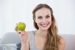 Happy young woman sitting on sofa holding green apple - stock photo