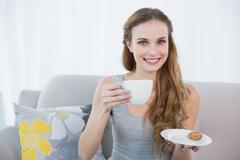 Cheerful young woman sitting on sofa holding cup and saucer - stock photo