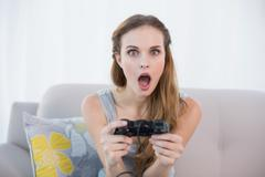 Shocked young woman sitting on sofa playing video games Stock Photos