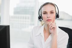Thoughtful call centre agent looking at camera Stock Photos