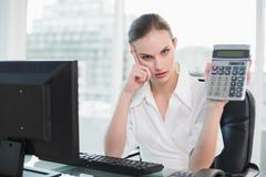 Frowning businesswoman showing calculator sitting at desk Stock Photos