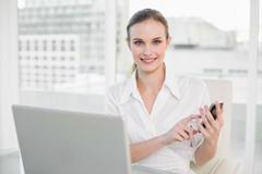 Smiling businesswoman using laptop and texting on smartphone - stock photo