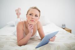 Natural thoughtful blonde lying on bed holding tablet - stock photo