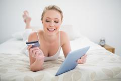 Natural smiling blonde lying on bed holding tablet and credit card - stock photo