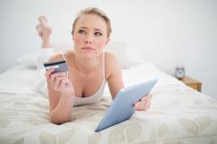 Natural thoughtful blonde lying on bed holding tablet and credit card Stock Photos