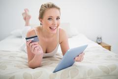 Natural cheerful blonde lying on bed holding tablet and credit card - stock photo