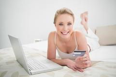 Natural cheerful blonde holding credit card and looking at camera - stock photo
