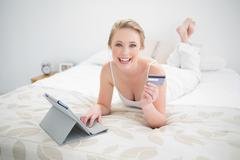 Stock Photo of Smiling natural blonde lying on bed and using tablet and credit card