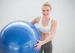 Stock Photo of Cheerful sporty blonde holding exercise ball