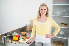 Smiling cute blonde standing hand on hips - stock photo