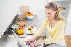 Stock Photo of Smiling cute blonde typing on her laptop