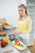 Smiling cute blonde holding cover of a pot - stock photo