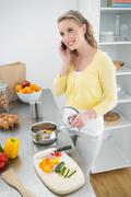 Stock Photo of Smiling cute blonde phoning and making dinner