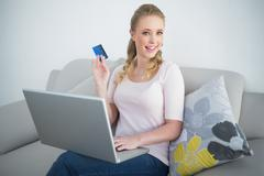 Casual happy blonde holding laptop and credit card - stock photo