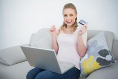 Casual thrilled blonde holding credit card and laptop - stock photo