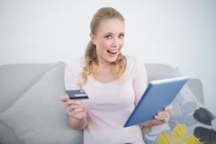 Casual thrilled blonde holding tablet and credit card - stock photo