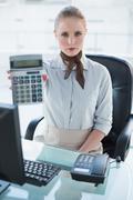 Blonde stern businesswoman showing calculator Stock Photos