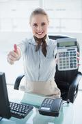Blonde smiling businesswoman showing calculator and thumb up Stock Photos