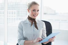 Stock Photo of Blonde cheerful businesswoman using tablet