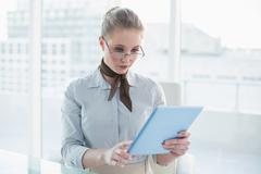 Blonde stern businesswoman looking at tablet - stock photo
