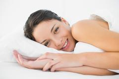 Smiling casual brunette lying in her bed - stock photo