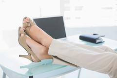 Close up of a businesswoman in high heels relaxing with feet up - stock photo
