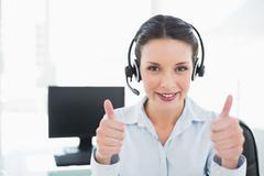 Stock Photo of Cheerful stylish brunette operator giving thumbs up