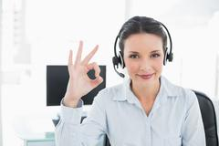 Stock Photo of Joyful stylish brunette operator making an okay gesture