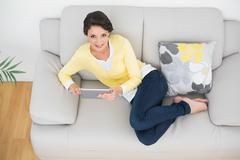 Delighted casual brunette in yellow cardigan using a tablet pc - stock photo