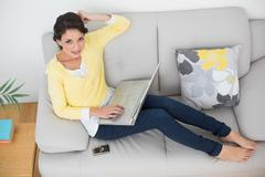 Stock Photo of Happy casual brunette in yellow cardigan using a laptop