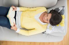 Content casual brunette in yellow cardigan reading a book - stock photo
