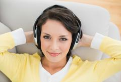 Smiling casual brunette in yellow cardigan enjoying music - stock photo